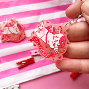 "Image of a pair of acrylic dangle earrings, hanging on fish hooks attached to a pink backing cards which reads ""drop earrings"". The earrings depict an illustration of a cute dog dressed like cupid. There is a red banner under the dog with white lettering which reads ""love yourself"". They have been printed onto frosted pink acrylic."