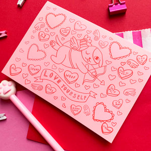 "Image of an A6 greeting card on a pink and red background. The print depicts a digital illustration of a dog dressed as cupid with a bow, arrow and wings. There are motifs of hearts and love heart sweets surrounding the composition. There is a banner below the dog with hand lettering which reads ""love yourself"". The line work is red with a pink background. It comes with a red recycled envelope."