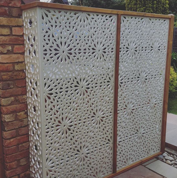 Cream geometric Moucharabiya screens installed to hide a hot tub in a garden