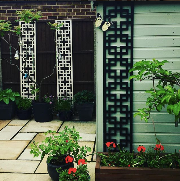 Two cream and one black geometric Cubed trellises by Screen With Envy installed in a garden