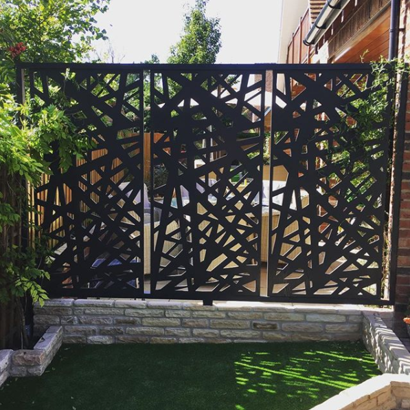 Garden privacy screens installed near seating area. Privacy screens by Screen With Envy