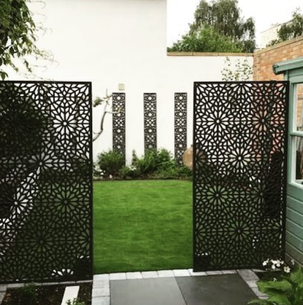 Two stylish designer black screens by Screen With Envy installed freestanding in a garden
