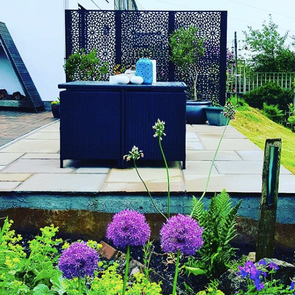 Black Geometric garden screens providing privacy around an outside seating area by Screen With Envy