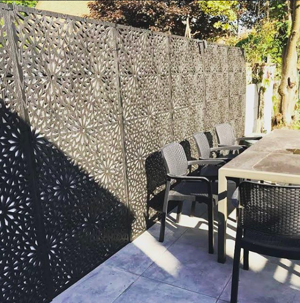 Run of designer geometric garden Screens by Screen With Envy used to provide privacy around an outside dining table