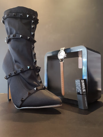 Black high heels and watch on table