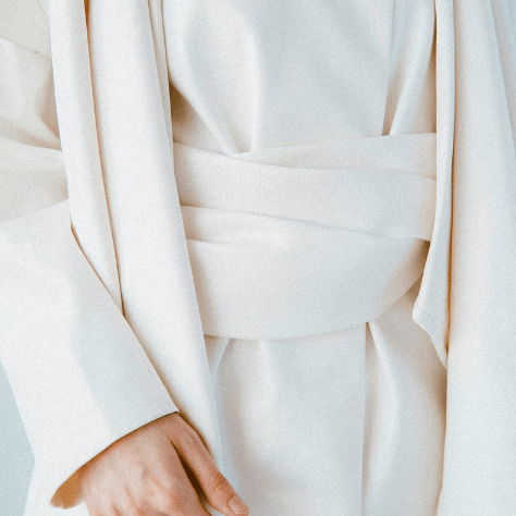 closeup picture of a womans torso whilst she wear a white dress and her right hand is showing