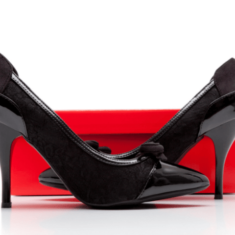Pair of black high heels facing each other with a red narrow shoe box in the background
