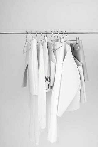 white clothes hanging on a clothing rail against a white background