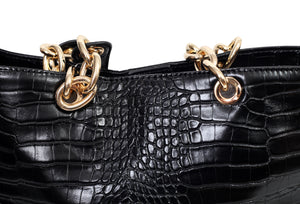 Close up view of a croc effect handbag and its metal detail handle