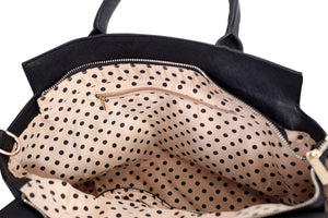 Inside view of a white and black tote handbag showing its polka dot lining and inside pockets