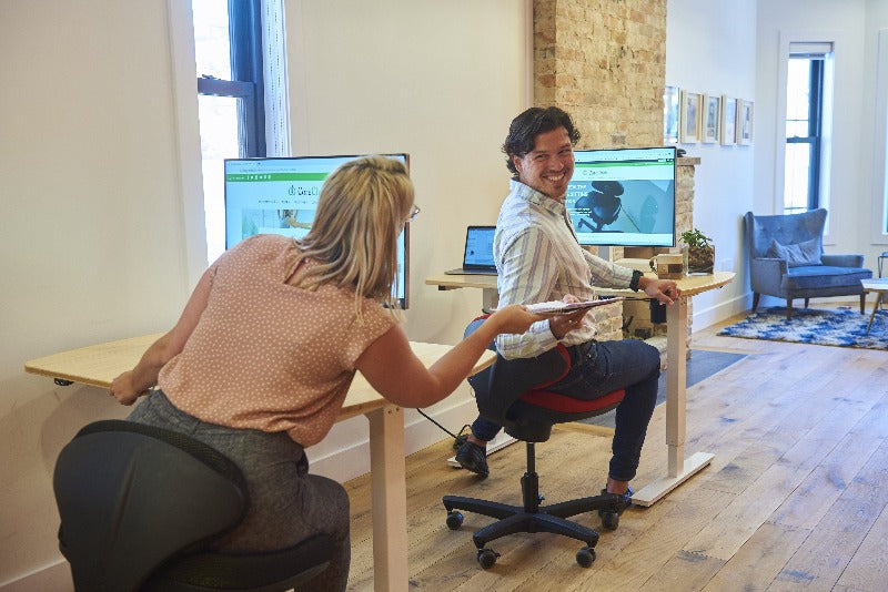 CoreChair Tango in the office, stretching while chatting with coworkers from Active Goods Canada