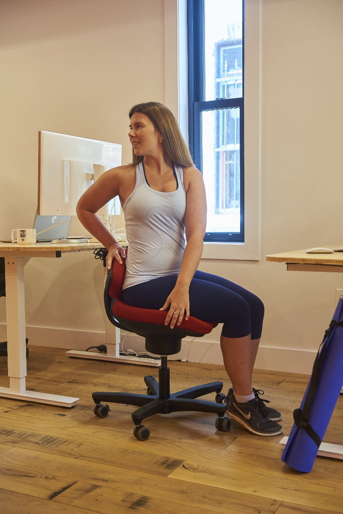 CoreChair Tango in red. Using the Tango to stretch while at work from Active Goods Canada