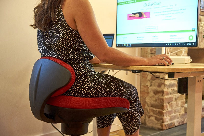 CoreChair Tango in Red, sitting down at office desk from Active Goods Canada