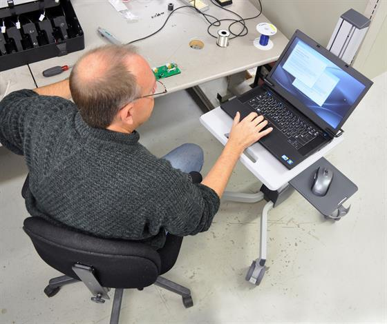 Man using mobile laptop cart at his desk
