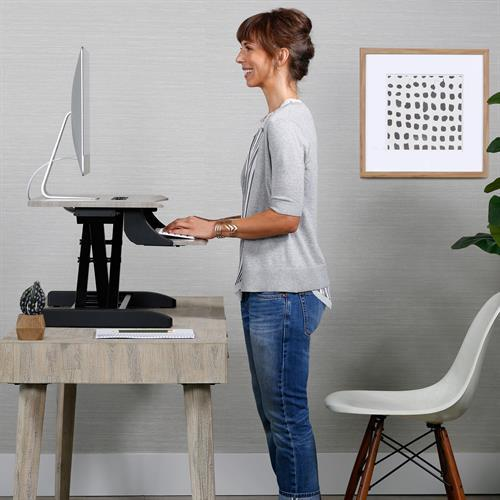 Woman using Ergotron WorkFit-Z Mini Sit-Stand Desktop. Fitneff Canada
