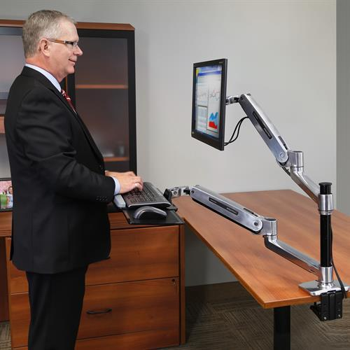 Man using WorkFit-LX, Sit-Stand Desk Mount System. Fitneff Canada