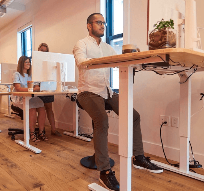 CorePerch Active Stool perching at standing office desk by Active Goods Canada