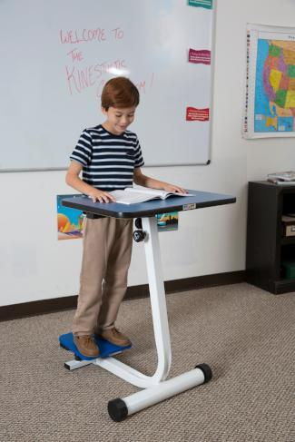 Boy using KidsFit Balance Desk from Fitneff Canada in classroom