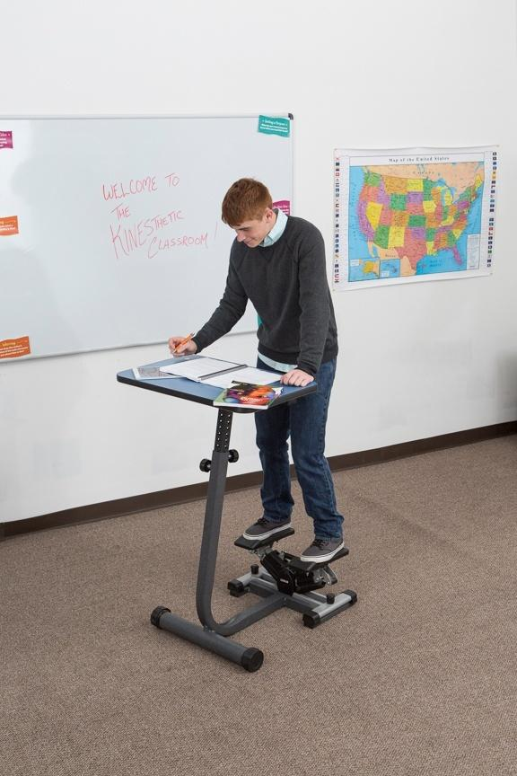 Boy using KidsFit Stepper Desk from Active Goods Canadain classroom