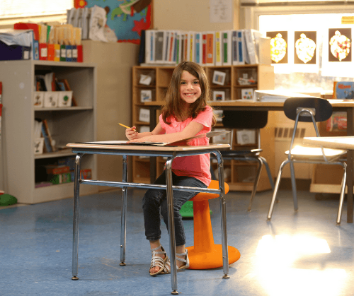 "Girl sitting on Kore Pre-Teen Wobble Chair 18.7"" in classroom"