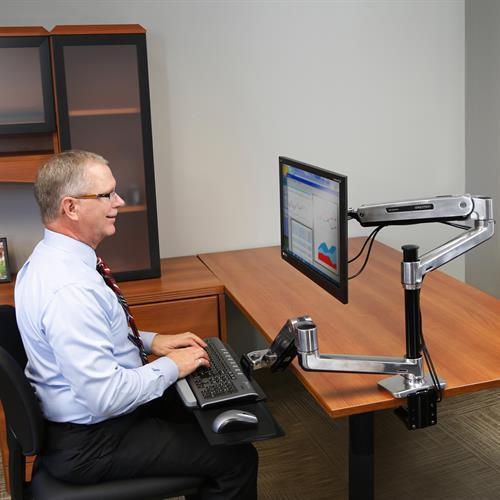 Man sitting at WorkFit-LX, Sit-Stand Desk Mount System. Fitneff Canada