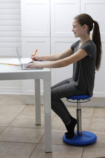 Girl using Kore Kids Height-Adjustable Wobble Chair at desk from Active Goods Canada