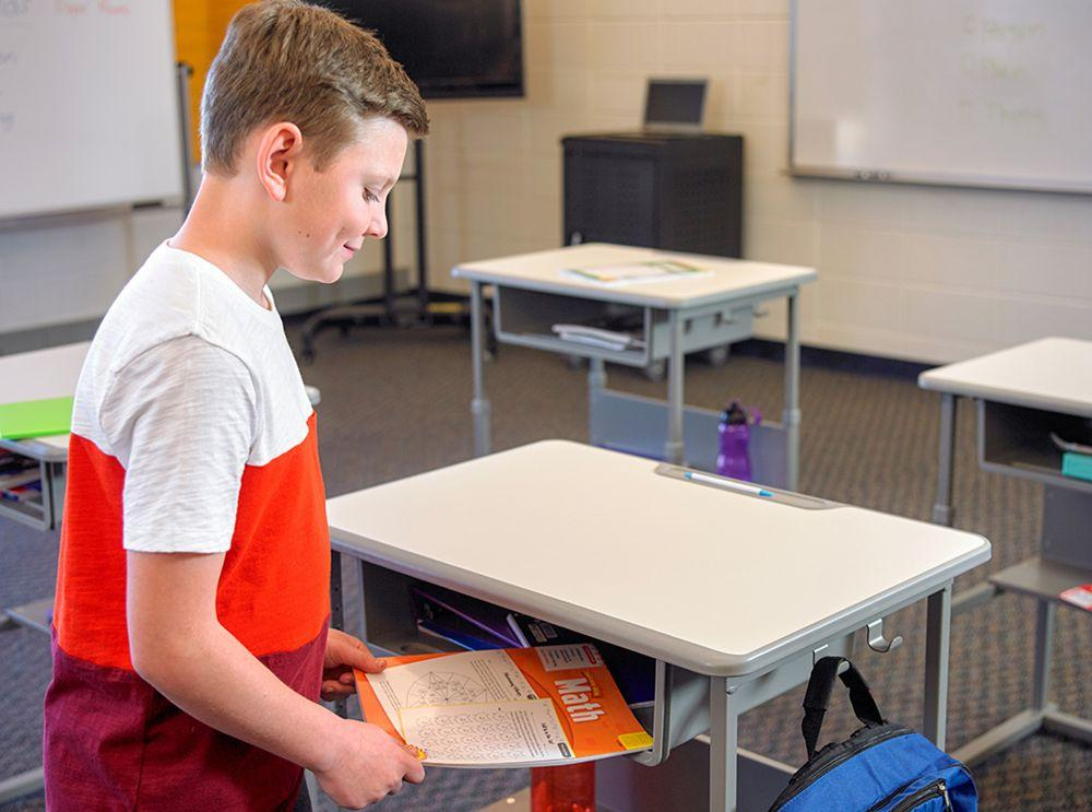 Boy using height-Adjustable Student Desk from Fitneff in classroom