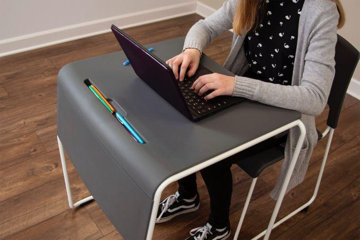 Student using the Luxor Lightweight Stackable Student Desk and Chair by Fitneff Canada