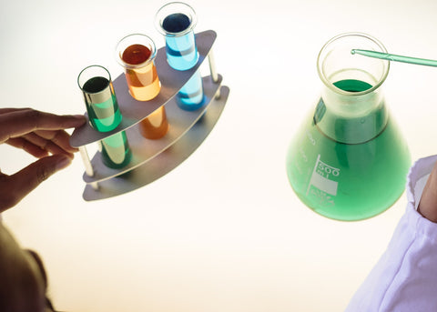 A beaker with a stand containing 3 flasks with colored liquid