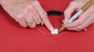 woman demonstrating how to cut mosaic tiles to fit in a circle