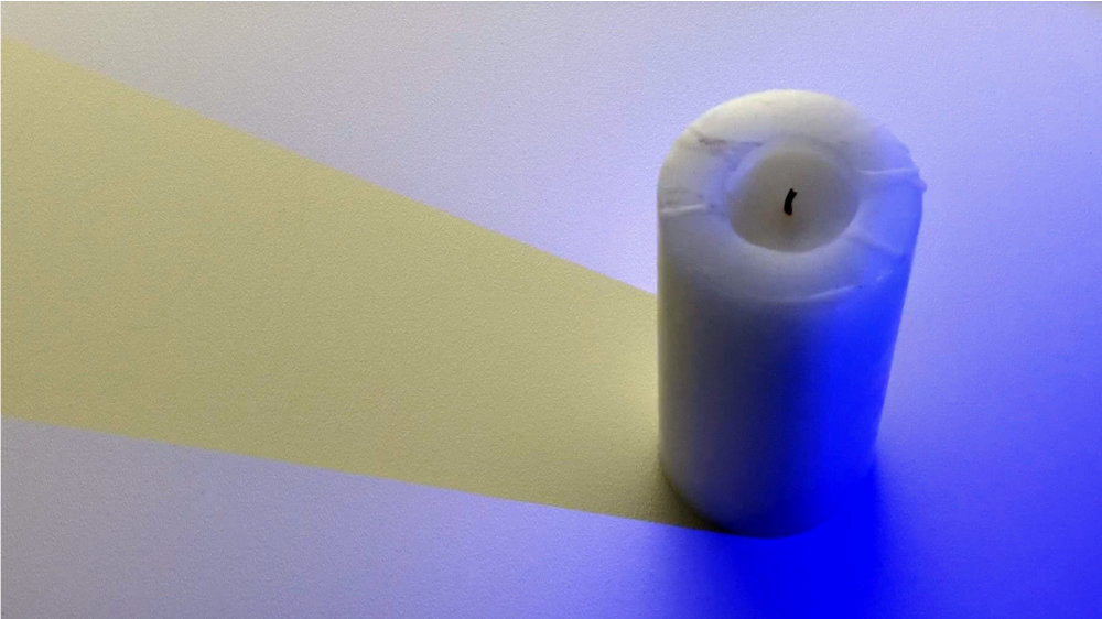 Candle with a blue light on it casting a yellow shadow