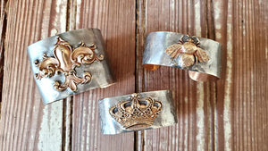Three sterling silver cuff bracelets by Heather Elizabeth, one with crown, one with bee, one with fleur de lis
