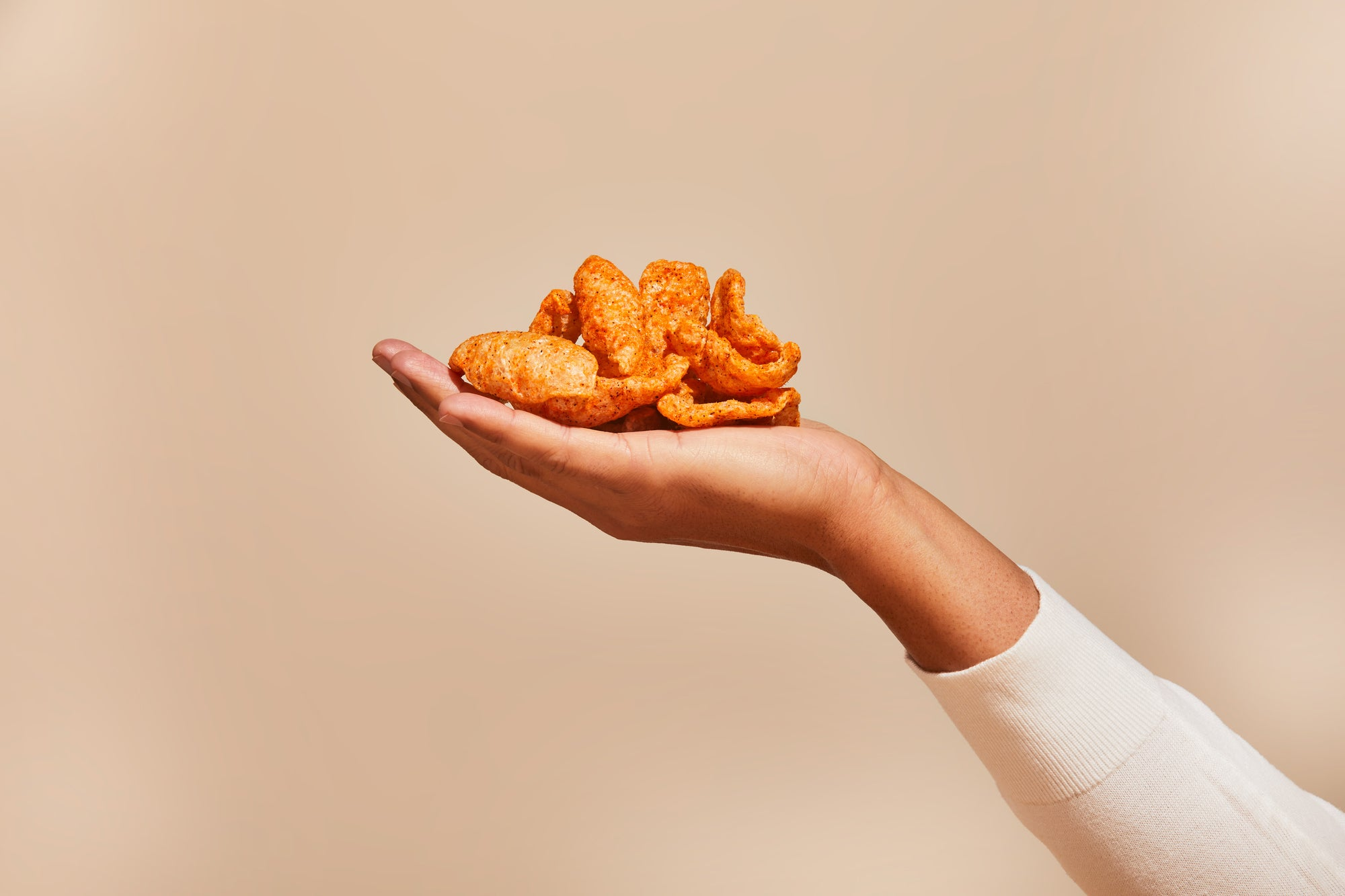 A delicious, crunchy stack of fried chicharrones in the palm of your hand