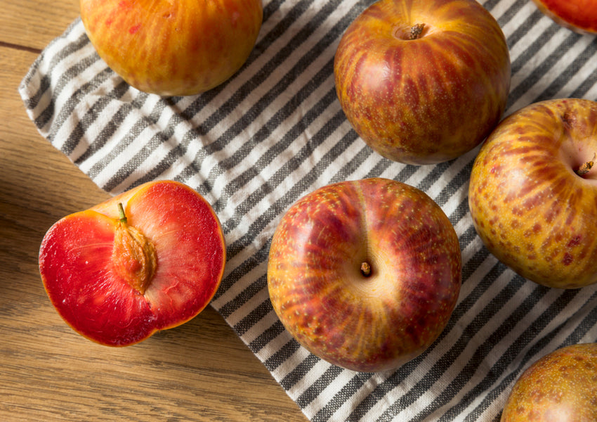 Whole and sliced pluots on dish towel