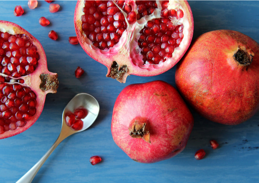Sliced and whole pomegranate on blue background