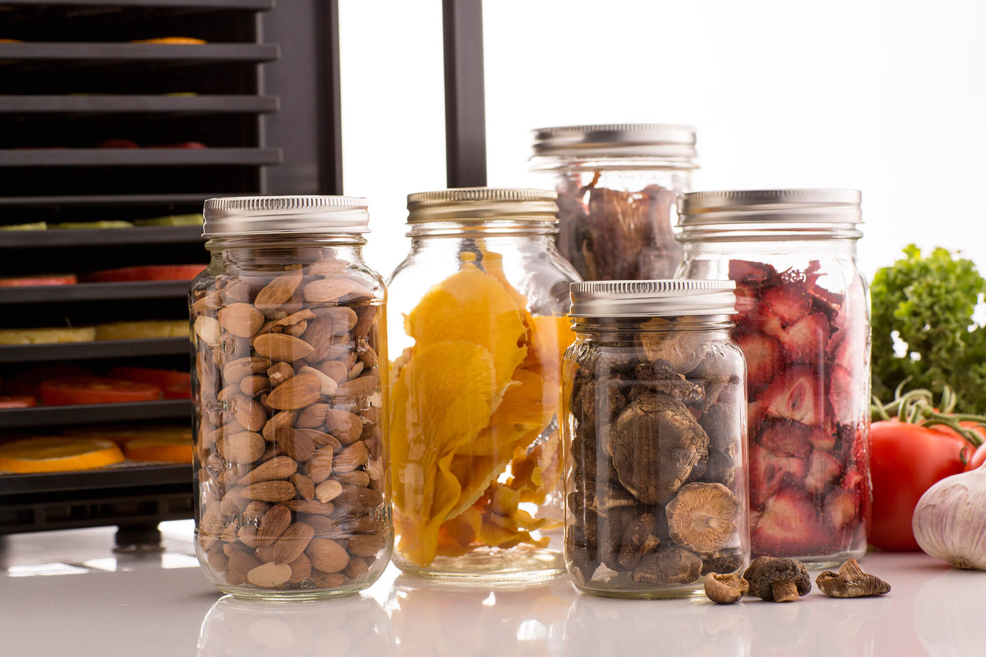 Glass jars filled with dried produce in front of an Excalibur RES10 dehydrator.