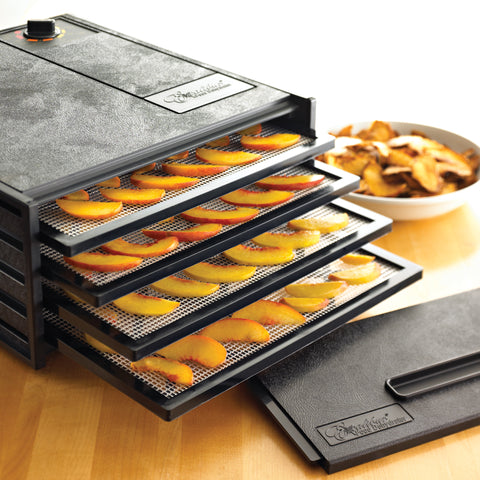 Sliced peaches on trays of a 4 tray Excalibur dehydrator.
