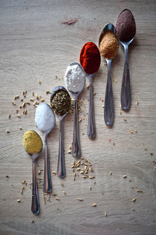 Assorted spices on spoons.