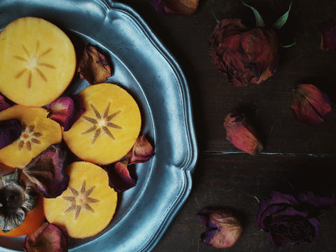 Dried fruit and flowers on a sliver plate.