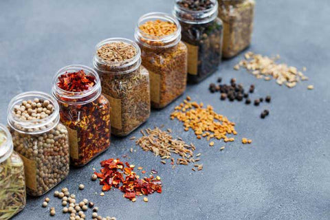 A variety of dried herbs and spices in jars for storage.