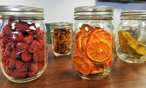 Mason jars containing dehydrated fruit, oranges, and raspberries.