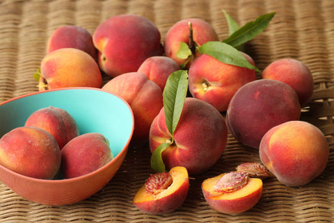 Fresh peaches spilling out of a bowl on a table.