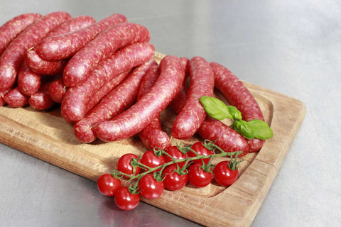 Sausages on a wooden board with tiny tomatoes.