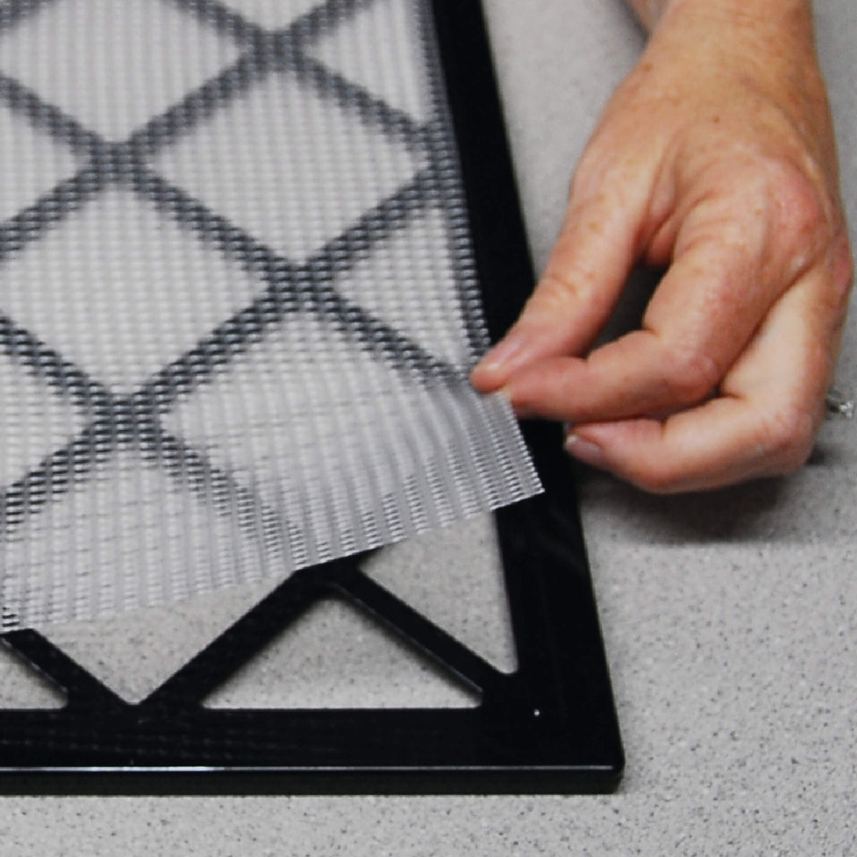 Excalibur dehydrator mesh sheet on a tray with the corner of the sheet being lifted.