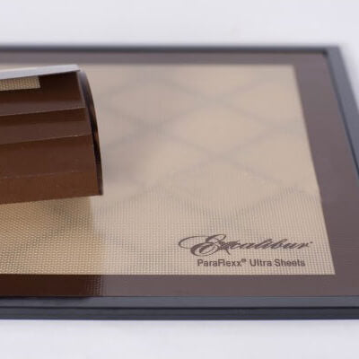 Excalibur Paraflexx Ultra silicone dehydrator drying sheet on a tray with a roll of sheets placed on top.