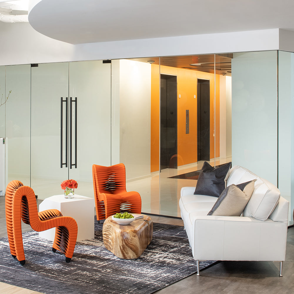 Contemporary office waiting room with orange chairs and white leather sofa - Jamie Merida Interiors