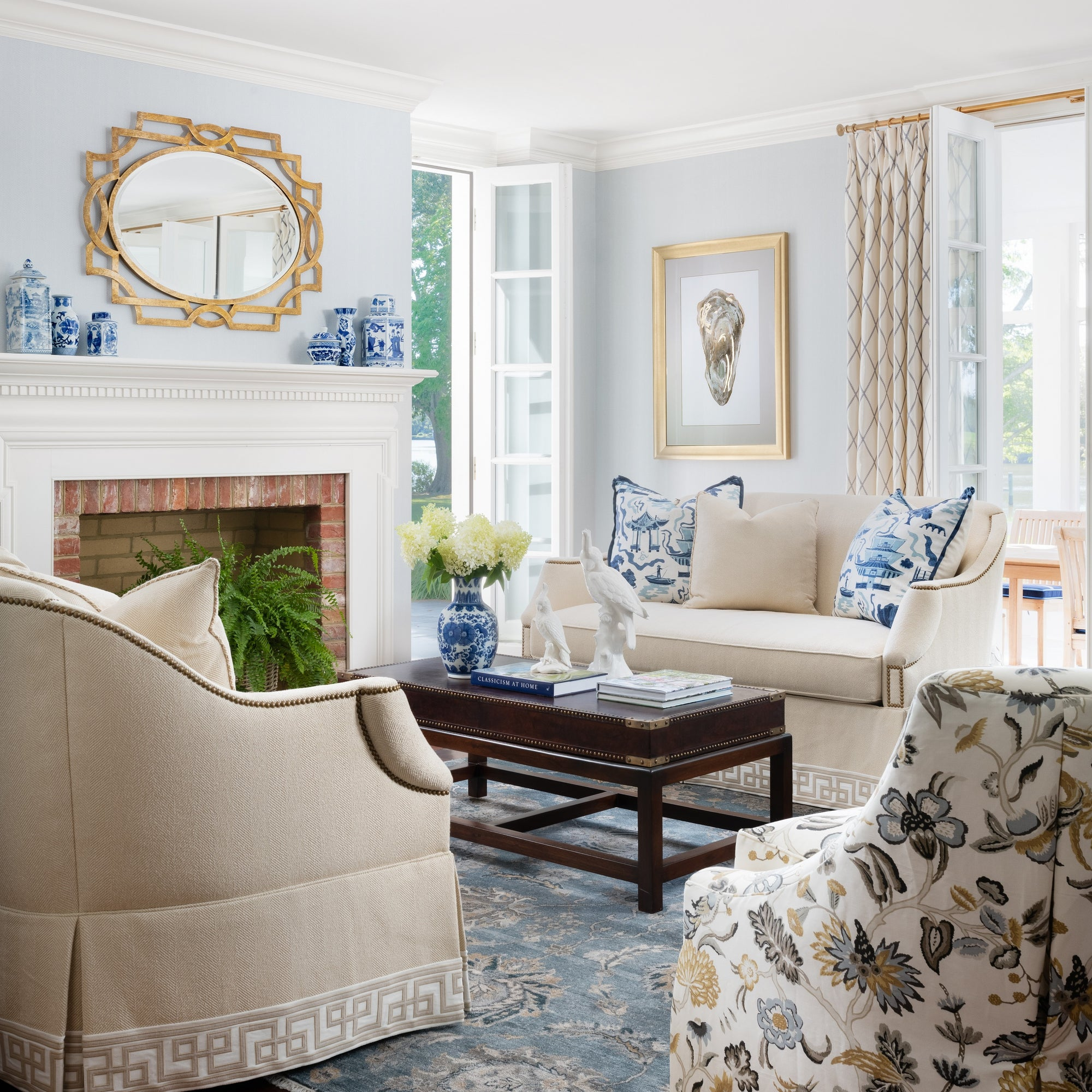 Traditional living room with blue walls and accents, neutral furniture, and natural light. Design by Jamie Merida Interiors.