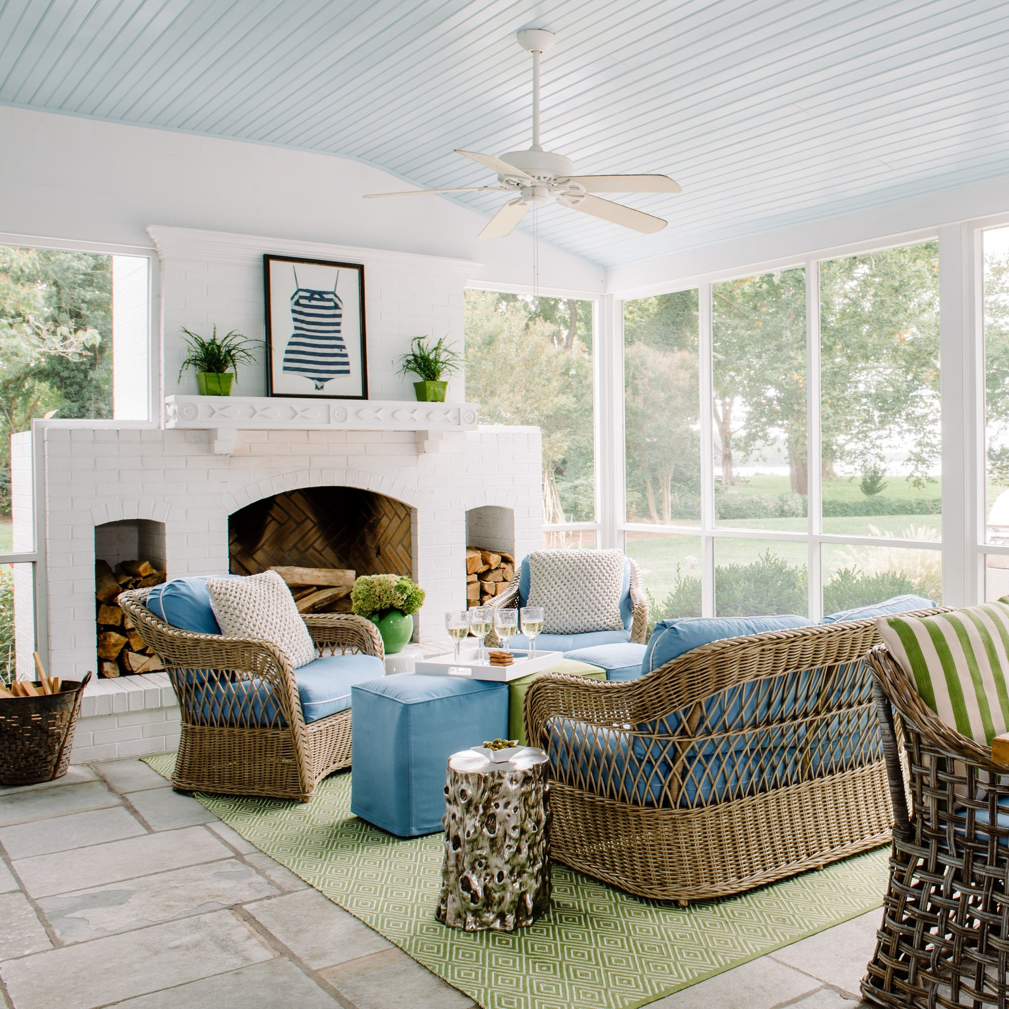 Large porch with white fireplace, soft blue ceiling and wicker furniture with green and blue accents. Interior design by Jamie Merida.