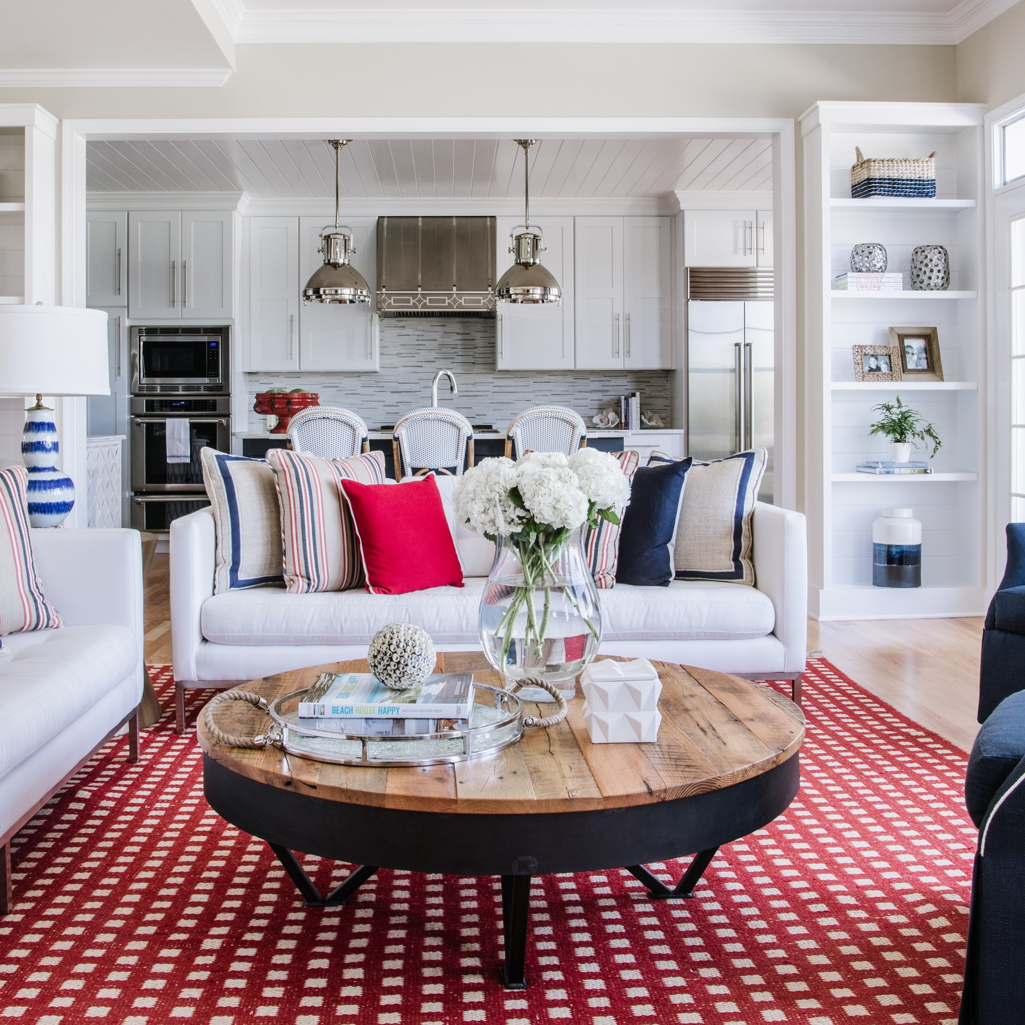 Eastern Shore modern luxury by Jamie Merida Interiors - shows red, white, and blue sitting room with nautical style; kitchen in background