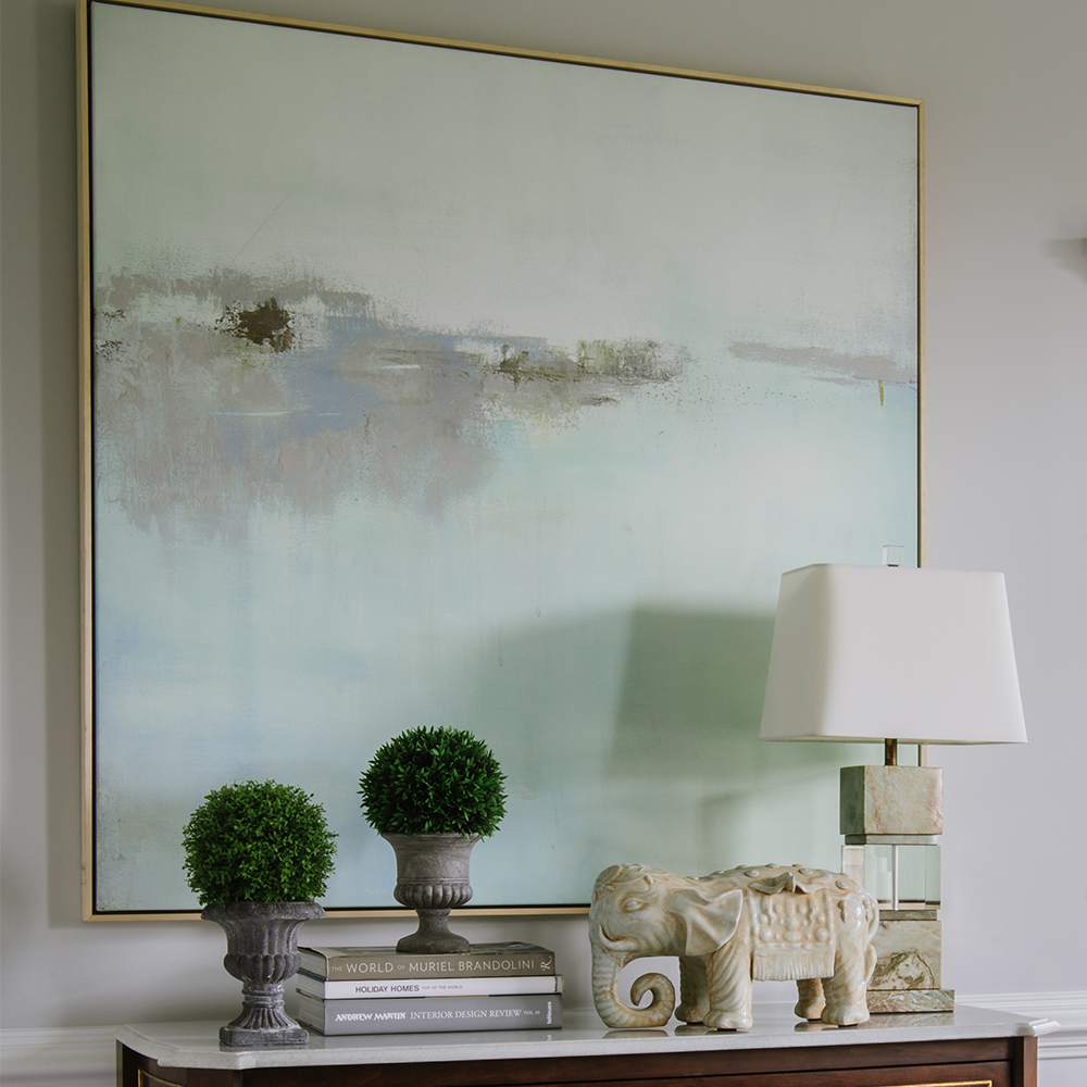 Art & wall decor at Bountiful Home - abstract painting in soft colors above an entry table with a lamp and home accessories